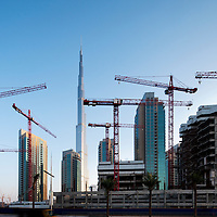 United Arab Emirates, Dubai, Burj Khalifa, the tallest building in the world, looms above construction sites and cranes at sunrise