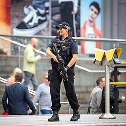 © Licensed to London News Pictures . 17/06/2018. Manchester , UK . Armed police in Exchange Square as the 2018 Manchester Day parade , celebrating Manchester's cultural and social life and diversity, passes through Manchester City Centre . Photo credit : Joel Goodman/LNP
