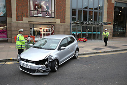 © Licensed to London News Pictures. 23/10/2015. Guilford, UK. A damaged car sits in front of The Friary Centre after a number of shoppers were injured. A child's shopping buggy is visible by the entrance to the shopping centre.  Photo credit: Peter Macdiarmid/LNP