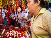 "17 FEBRUARY 2015 - BANGKOK, THAILAND:  People shop for Chinese New Year decorations on Yaowarat Road in Bangkok's Chinatown. Chinese New Year is February 19 in 2015. It marks the beginning of the Year of Sheep. The Sheep is the eighth sign in Chinese astrology and the number ""8"" is considered to be a very lucky number. It symbolizes wisdom, fortune and prosperity. Ethnic Chinese make up nearly 15% of the Thai population. Chinese New Year (also called Tet or Lunar New Year) is widely celebrated in Thailand, especially in urban areas like Bangkok, Chiang Mai and Hat Yai that have large Chinese populations.      PHOTO BY JACK KURTZ"