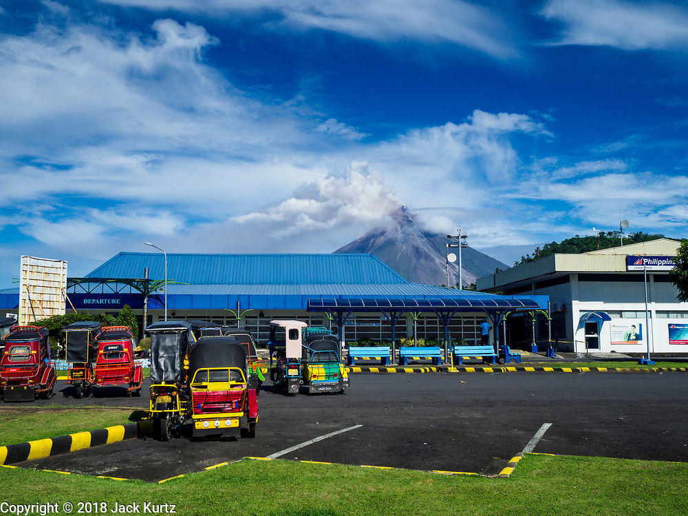 25 JANUARY 2018 - LEGAZPI, ALBAY, PHILIPPINES:  A small eruption takes place in the Mayon volcano as seen from the airport in Legazpi. The airport in Legazpi is closed until at least 31 January 2018 because of the volcano's eruptions. The volcano continued to erupt Thursday. More than 60,000 people have been evacuated because of the volcano.     PHOTO BY JACK KURTZ