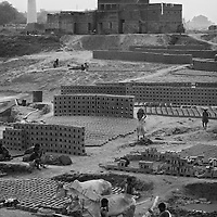 A brick kiln in the Sadar area of Patna city. All of Bihar's brick kilns are covered as part of the Unicef SIA (Supplementary Immunisation Activity - ie. the week of the polio round, 12-16th November 2006). Workers at Bihar's kilns are often seasonal migrants and are therefor risk missing vaccination rounds. Their traveling makes it imperative that they are immunised for fear of spreading the virus. Many kilns employ over twenty families with some employing over fifty. In Patna district in the May 2006 polio vaccination round there were 30,746 children immunised at brick kilns. In Bihar state in the May 2006 polio vaccination round there were 173,997 children immunised at brick kilns. ..Photo: Tom Pietrasik.Patna, Bihar, India..November 16th 2006