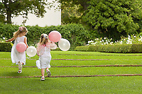 Two young girls running in garden holding balloons back view