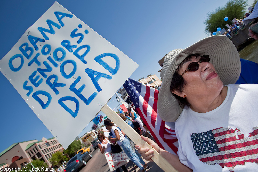 Aug. 8, 2009 -- SCOTTSDALE, AZ: People carry signs expressing their opposition to the Obama health care plan at a rally in Tempe, AZ. Nearly 1,000 people opposed to the President Barack Obama's health care reform efforts picketed the offices of Congresman Harry Mitchell (D-AZ) in Scottsdale, AZ, Saturday. The protest was organized by conservative groups who are organizing similar protests against President Obama across the US. Ostensibly concerned mostly with health care reform, it was also a protest against almost everything related to the Obama administration. Photo by Jack Kurtz / ZUMA Press