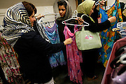 Although she will never be able to wear it in public, a teenager debates between two brightly-colored and revealing dresses at Kasa, one of the most famous women's clothing stores in Tehran. Young stylish women come to buy the latest in manteaus, or long lightweight  jackets and roosary, beautiful scarves in the latest colors and patterns.