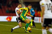West Bromwich Albion forward Dwight Gayle (16) shields the ball from Sheffield United midfielder John Fleck (4)  during the EFL Sky Bet Championship match between Sheffield United and West Bromwich Albion at Bramall Lane, Sheffield, England on 14 December 2018.