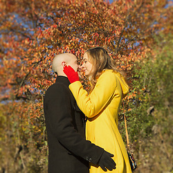 A cute couple sharing an embrace among the fall colours.