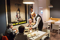 "MILANO, ITALY - 1 MARCH 2016: Said Manah, an inmate and waiter, serves dinner to customers of the ""InGalera"" restaurant in the Bollate prison in Milan, Italy, on March 1st 2016.<br /> <br /> ""InGalera"" (which translates in English as ""InJail"") is the first restaurant located inside a prison and offering high-quality cooking to the public and a future to the inmates. It was inaugurated last October inside the Bollate prison in Milan. It is open five days a week for lunch and dinner, and seats 55 people. There are 9 people involved in the project, including cooks and waiters, all regularly employed and all inmates of the prison, apart from the chef and the maître d'hôtel, recruited from outside to guarantee the high quality of the food served. The restaurant is a project of the co-operative ABC La Sapienza - that operates inside the prison and provides more than 1,000 meals three times a day with the help of inmates they've hired - and of PwC, a multinational operating in the field of corporate consultancy. The goal of this project is to follow prisoners in rehabilitation process of social inclusion.<br /> <br /> The Bollate prison is already known for being a good example of penitentiary administration. The inmates are free to move around from one area to the other inside the prison (their cells open at 7:30am and close at 9pm) to go study, exercise in a gym, or work (in a call center, as scenographers, tailors, gardeners, cooks, typographers, among others)  in one of the 11 co-operatives inside the prison or in one of the private partnering businesses outside the prison. The turnover of the co-operatives that work inside the prison was €2mln in 2012."