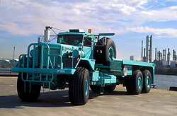 Large turquoise flatbed transport truck sitting parked on a dock at the Port of Houston