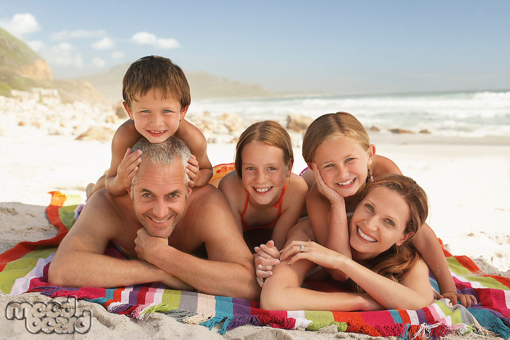 Family lying on beach.