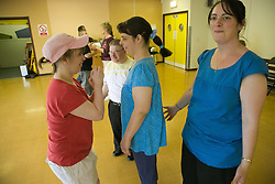 Group of Day Service users with learning disability enjoying a line dancing class encouraged by Day Service Assistant,