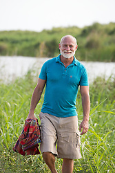 mature man with a white beard and mustache walking through the tall grass of The Everglades in Florida