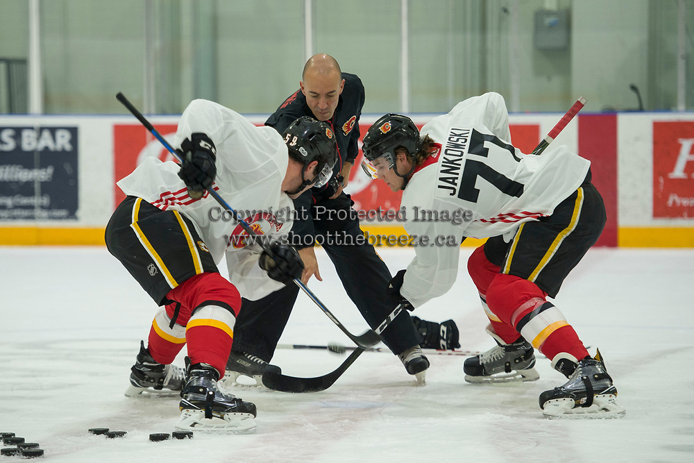 PENTICTON, CANADA - SEPTEMBER 8: Head coach Ryan Huska of Calgary Flames runs through face off drills during morning skate with Dillon Dube #59 and Mark Jankowski #77 on September 8, 2017 at the South Okanagan Event Centre in Penticton, British Columbia, Canada.  (Photo by Marissa Baecker/Shoot the Breeze)  *** Local Caption ***