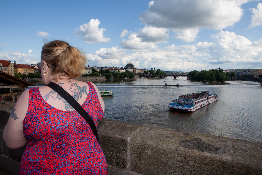 A tattooed lady visiting Charles Bridge. The Charles Bridge (Czech: Karlův most) is a famous historic bridge that crosses the Vltava river in Prague, Czech Republic and is probably the Nr.1 tourists magnet in the city.