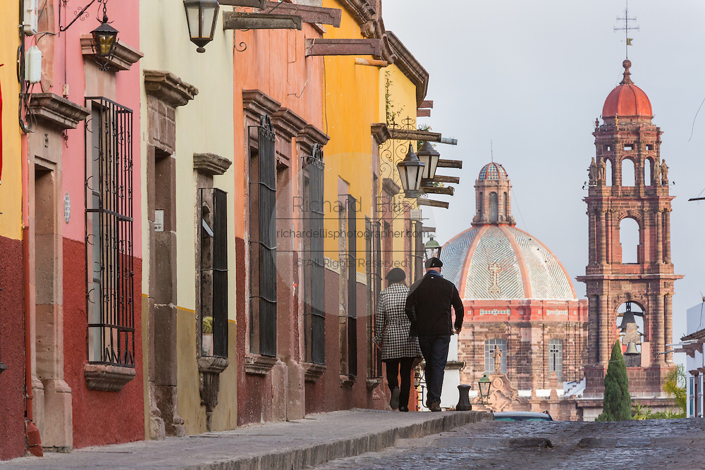 Pedestrians walk toward the dome of Las Monjas Church dome and spire of the San Francisco Church in the historic center of San Miguel de Allende, Mexico.