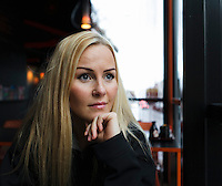 Young woman in a restaurant looking out the window.