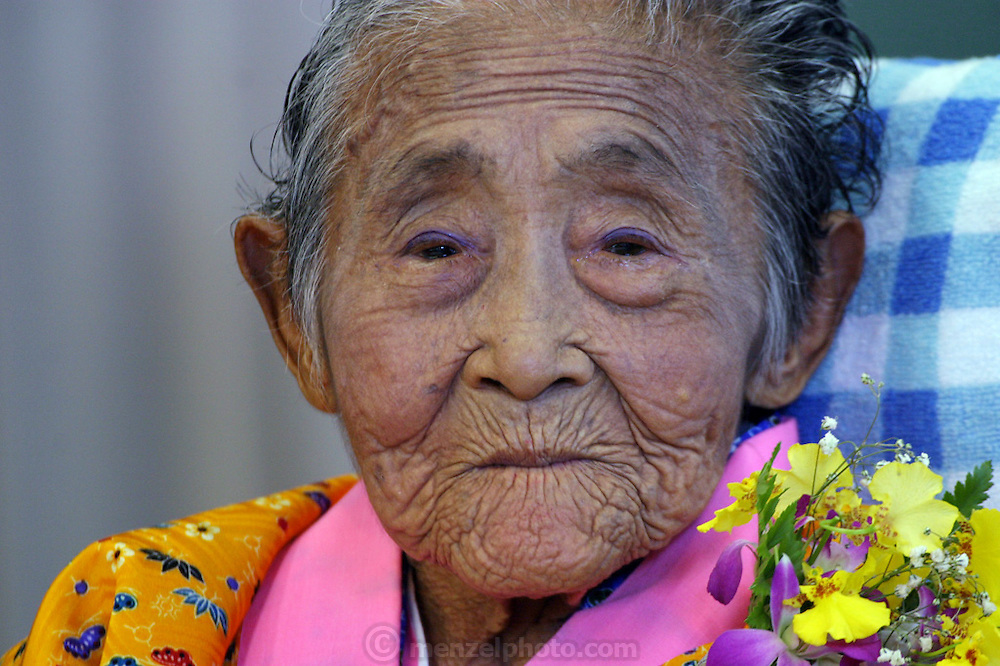 Matsu Zakimi (with purple eyeshadow applied by her great-granddaughter) during the celebration for her 97th birthday,at a nursing home near Ogimi Village. Most of the community has turned out to honor the birthdays of three residents. (These are traditional Japanese birthdays, not the actual birth dates; 88, for example is celebrated on the eighth day of the eighth month in the lunar calendar.) Musicians, dancers, and comedians perform as well wishers cheerfully gorge on sushi, fruits, and desserts washed down with beer and saki. (Supporting image from the project Hungry Planet: What the World Eats).