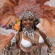 Tropicalfete Body of Vibration Dance and Theater, portrait  smiling African American Caribbean dancer wearing feathers headdress.
