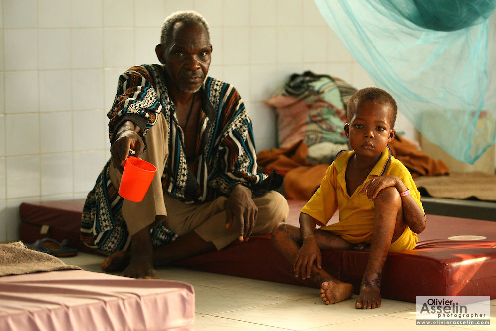 Abubakar Barrie, 8, a severely malnourished child,and his father Chernor Anhusine Barrie at the therapeutic feeding center of the Magbenthe hospital in Makeni, Sierra Leone on Thursday February 26, 2009. UNICEF sponsored some of the construction of the hospital facilities, and also provides high-protein biscuits and milk as part of a joint effort with the World Food Programme..
