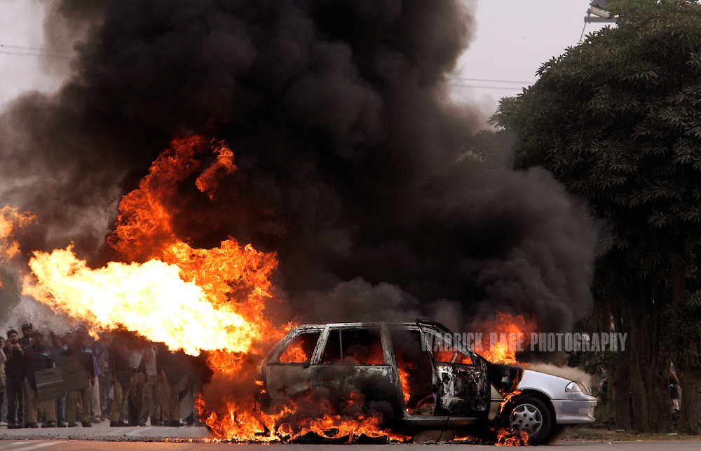 LAHORE, PAKISTAN - NOVEMBER 13: The gas tank of a car explodes after it caught fire when Pakistan People's Party supporters accidently set fire to the car, while trying to set tires alight as a sign of protest near the house of former Prime Minister Benazir Bhutto November 13, 2007 in Lahore, Pakistan. Bhutto was put under house arrest the night before a planned 'Long March' with supporters from Lahore to Islamabad. She called upon President Pervez Musharraf to resign as president and head of the army and ruled out taking part in any Musharraf government. (Photo by Warrick Page)