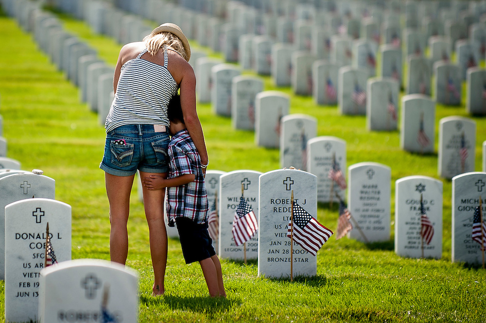 A mother stands with her son near the grave of his father on Thursday afternoon in Arlington National Cemetery. The Memorial Day weekend will bring thousands of people to the cemetery to mourn and honor the loss of their loved ones.