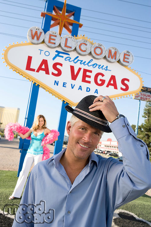 Portrait of mid-adult man in front of Welcome to Las Vegas sign, mid-adult woman in background.
