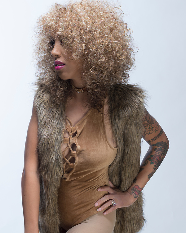 Female fashion model against a white background posing in a brown one piece, fur vest and brown tights.