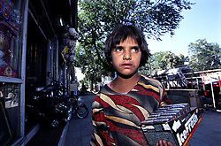 A young girl sells chewing gum  near a toy-shop in Shar-e-Naw, Kabul