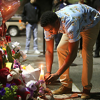 Kawayne Hunter lays flowers at a makeshift memorial to honor deceased Orlando Police officer Master Sgt. Debra Clayton who was shot and killed as she attempted to stop and question accused gunman Markeith Loyd, at an Orlando Walmart, on January 10, 2017 in Orlando, Florida. Orange County deputy Norm Lewis who was also killed on his motor patrol while responding to Clayton's shooting was also honored.  (Alex Menendez via AP)