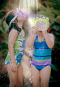 Two girls playing under outdoor shower with swimming masks
