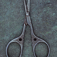 Antique steel sewing scissors decorated with small pattern lying on tarnished metal