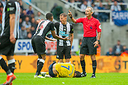 Isaac Hayden (#14) and Matt Ritchie (#11) of Newcastle United FC argue with referee Martin Atkinson, as Henrikh Mkhitaryan (#7) of Arsenal FC lies injured during the Premier League match between Newcastle United and Arsenal at St. James's Park, Newcastle, England on 11 August 2019.
