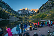 The Maroon Bells and yellow aspen leaves reflect in Maroon Lake. The Maroon Bells are two adjacent peaks of the Elk Mountains: Maroon Peak 14,163 feet on left, seen behind North Maroon Peak 14,019 feet, in Maroon Bells-Snowmass Wilderness of White River National Forest. The mountains are on the border between Pitkin County and Gunnison County, about 12 miles southwest of Aspen, in Colorado, USA.