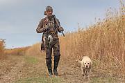 Successful waterfowl hunter walks with his dog.