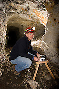 biologist Chris Loggers installs a motion sensor in the interior of the abandonded Smoking Dump gold mine. The sensor will help scientists understand why sensitive bat species like Townsend big-eared bats (Corynorhinus townsendii) use the mine for winter hibernation. Coleville National Forest, Washington.