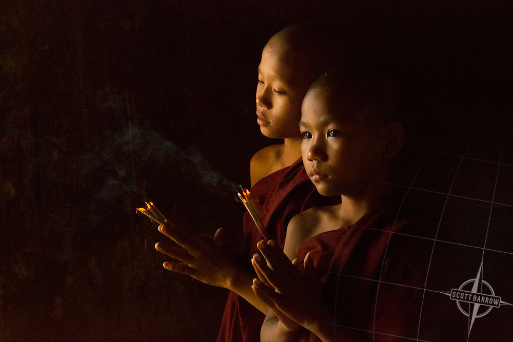 Young monks praying with incense in a temple or monastery. Myanmar.