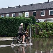 Foto: David Rozing Nederland Barendrecht 29 mei 2018 Wateroverlast door enorme hoosbuien clusterbui clusterbuien hoosbui. Man op fiets fietser fietst door ondergelopen straten. Code Oranje