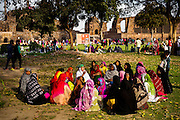 19th March 2015, New Delhi, India. A group of women chant and sing in the ruins of Feroz Shah Kotla in New Delhi, India on the 19th March 2015<br /> <br /> PHOTOGRAPH BY AND COPYRIGHT OF SIMON DE TREY-WHITE a photographer in delhi<br /> + 91 98103 99809. Email: simon@simondetreywhite.com<br /> <br /> The13th century fortress-city of Firoz Shah Kotla in Delhi is thronged weekly with thousands of supplicants seeking favour from supernatural beings of smokeless fire, - Djinns. These magical entities also known as Jinn, Jann or Genies spring from Islamic mythology as well as pre-Islamic Arabian mythology. They are mentioned frequently in the Quran and other Islamic texts and inhabit an unseen world called Djinnestan. Believers, mostly Muslim but from other faiths too, circumnavigate the ruins clutching dozens of photocopied requests, flower petals, incense, and candles. They visit the numerous niches and alcoves in the catacombs said to be occupied by different djinns and greet and salute the invisible occupants with offerings.  A copy of their requests, often with detailed contact information, photographs and even police reports to bolster the case is left with the 'Baba' before moving on to the next where the procedure is repeated - like making applications at different departments of a bureaucracy.