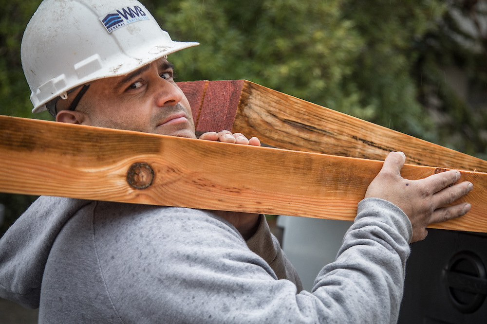 Construction crew member and Oakland resident Mike Diaz unloads timber at the site of the new Calistoga Teen Center at the corners of Grant and Stevenson Streets