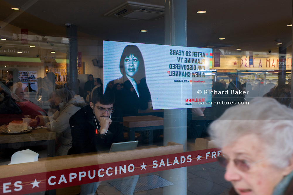 Mobile TV advertising billboard travels through central London and seen reflected in cafe window.
