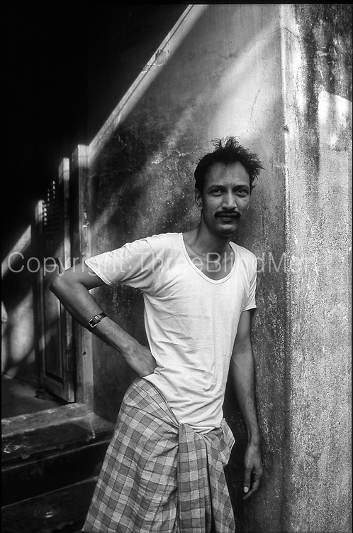 Man in doorway to his home in Chennai. Morning. looks a bit sleepy.