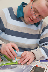 Client with Downs Syndrome doing craft activity at a resource for people with physical and sensory impairment.
