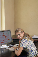 Woman smiling by computer in office