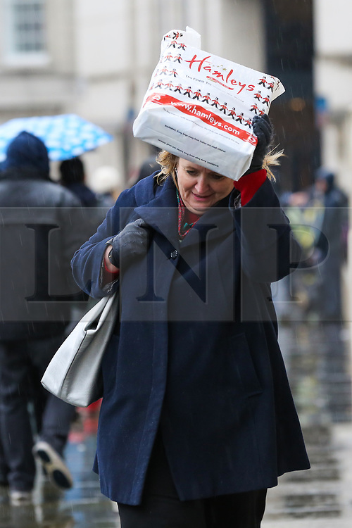 © Licensed to London News Pictures. 15/12/2018. London, UK. A woman shelters under a Hamlets bag during a wet, cold, blustery day in London. Photo credit: Dinendra Haria/LNP