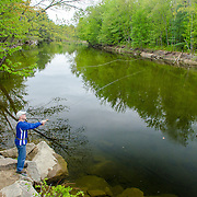 An eager fly fisherman casts a line into the chilly spring waters of the Saco River. North Conway, NH