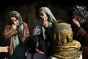Maryam, 38, (Centre) is talking to relatives in Mazar-i-Sharif, while being surrounded by her family and neighbours in front of the cave where they live since seven years, in Bamyan, an area mostly populated by Hazaras. A historically persecuted minority (15%) due to more lenient Islamic faith and characteristic 'Eastern' lineaments, Hazaras constitute the 70% of Bamyan's population. Halema, 9, (Left) one of Maryam's daughters is having regular toothache. Due to hard conditions of living and poverty, health issue are a major concern in the region.