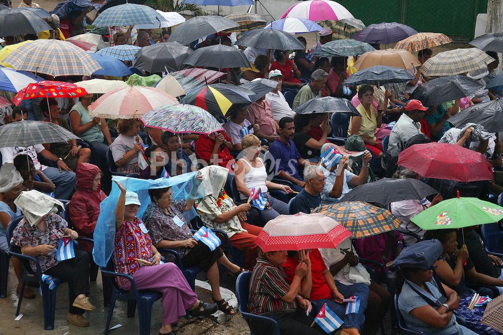 Crowd of spectators in the rain at revolutionary meeting; Havana; Cuba,