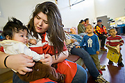 24 JANUARY 2010 -- WENDEN, AZ:  Red Cross Emergency Service Specialist Tiffany Buford (CQ) plays with Naomi Balcazar (CQ) 4 months old, at the shelter in Salome. Brittney's family lives in Wenden and was evacuated to Salome. Wenden was slammed by its second 100 year flood in 10 years on Thursday night when water raced through Centennial Wash and into the small town in La Paz County west of Phoenix. Most of the town's residents were evacuated to Red Cross shelters in Salome, about 5 miles west of Wenden.    PHOTO BY JACK KURTZ
