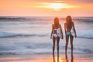 Two female surfers watching the sunset at Scripp's Beach, La Jolla Shores, San Diego, California Girls at La Jolla Shores, Scripp's Beach, San Diego, California