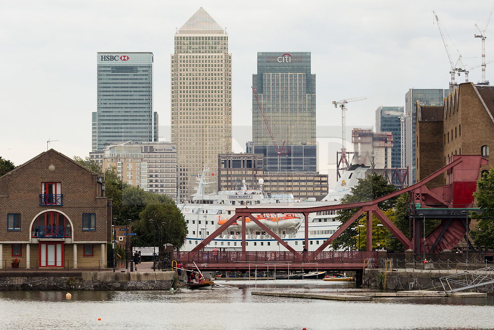 © Licensed to London News Pictures. 14/08/2017. LONDON, UK.  The large cruise ship, Ocean Majesty leaves London on the River Thames this evening, passing a residential area in east London and in front of the Canary Wharf skyscrapers. Ocean Majesty is approximately 445m long and carries up to 621 people. Environmentalists claim the pollution created by giant cruise ships travelling into the capital city outweigh their economic benefits. The Port of London Authority (PLA) are conducting a work programme during 2017 to monitor air quality and pollution caused by river traffic on the River Thames.  Photo credit: Vickie Flores/LNP